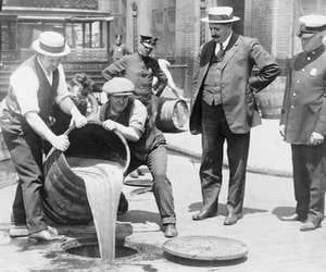 Black and white image of two men pouring a barrel of beer down a sewer hole, which an officer holds a man under arrest. Prohibition Pub Crawl Lower East Side